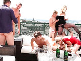 A group of busty babes and horny dudes drinking champagne on the roof and fondling one another