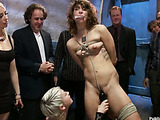 Curly brunette slut in a blue dress getting tortured and gangbanged in public