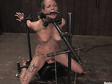 Tattooed blonde babe fixed in a special bdsm device sitting on a sybian