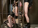 Ponytailed brunette vixen in a corset getting encaged before whipping and asspounding