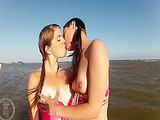 Two pigtailed teenies in bikini kissing on the air dolphin in the ocean
