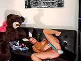 Long-haired hottie wearing bunny ears and a bunny tail butt plug plays with her clit.