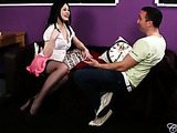 Sexy babe wearing white blouse, pink skirt, black stockings and high heels sits on a black couch with a handsome stud as they talk about a girl that he's seeing.
